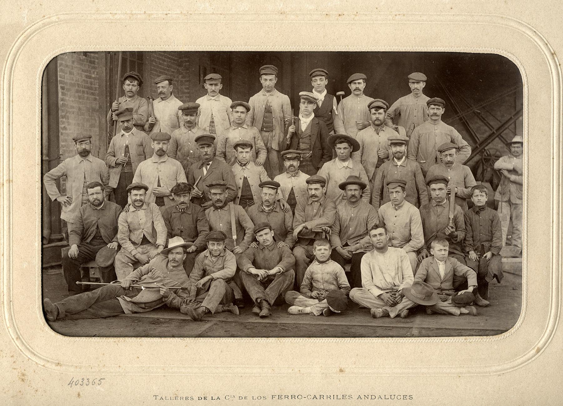 Retrato de un grupo de obreros y tres aprendices de Ferrocarriles Andaluces. Pertenece al reportaje realizado por el fotógrafo parisino J. David en los talleres malagueños de la compañía en 1903.